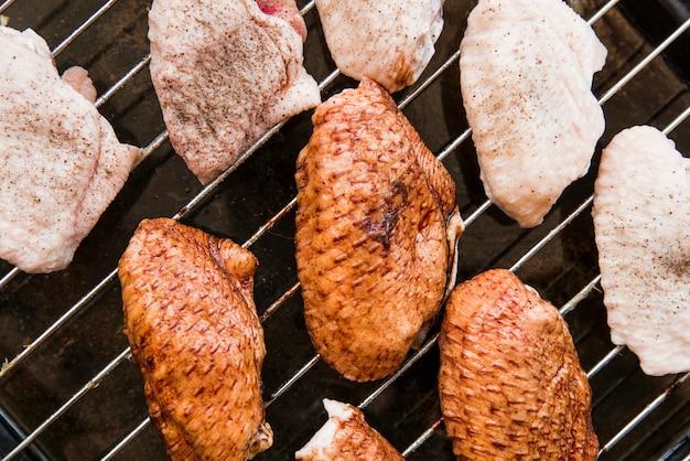 Vista superior das asas de frango cru na grelha de metal