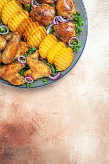 Vista superior das asas de frango, um apetitoso frango, batatas fritas, ervas e cebolas no prato