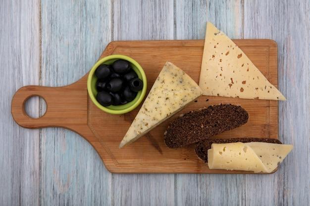 Vista superior das azeitonas com fatias de pão preto com queijos na tábua sobre fundo cinza