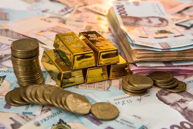 Vista superior das barras de ouro sobre o dinheiro ucraniano. uah. economize e conceito de dinheiro.