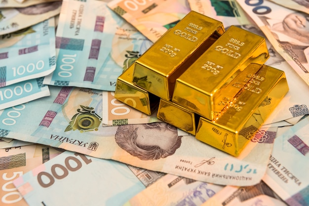Vista superior das barras de ouro sobre um fundo de dinheiro ucraniano. uah. economize e conceito de dinheiro. fundo financeiro