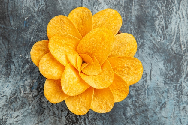 Vista superior das batatas fritas decoradas em forma de flor em uma tigela marrom na mesa cinza
