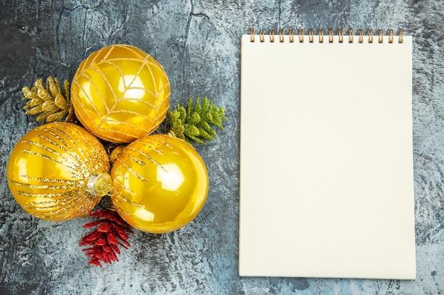 Vista superior das bolas da árvore de natal um caderno na superfície cinza