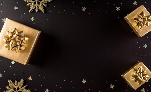 Vista superior das caixas de natal douradas em fundo preto com espaço de cópia para o texto