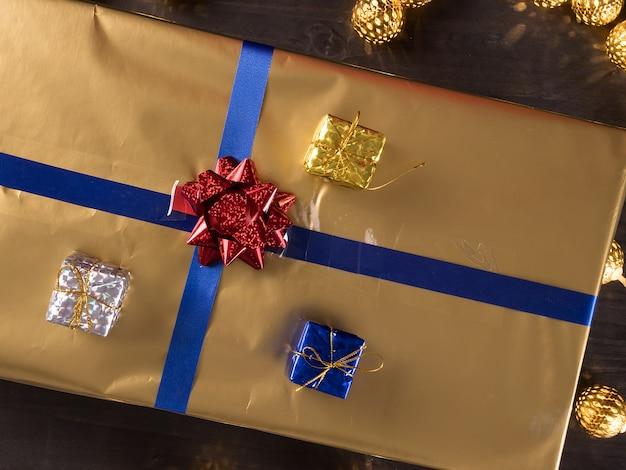 Vista superior das caixas de presente de natal douradas em fundo de madeira vintage velho. celebração de inverno