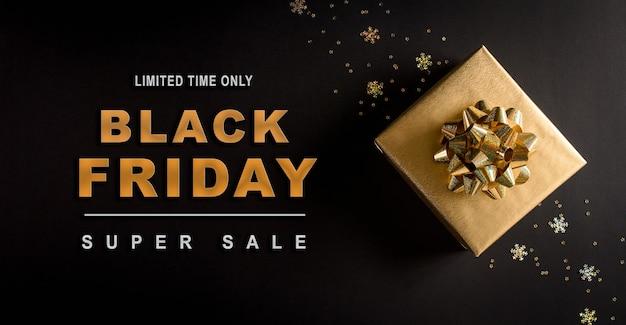 Vista superior das caixas de presente de natal douradas na superfície preta com o texto da black friday