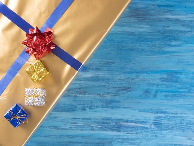 Vista superior das caixas de presente de natal douradas no antigo fundo de madeira azul vintage. celebração de inverno