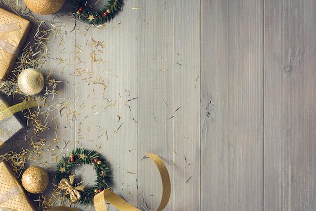 Vista superior das caixas de presente de natal e itens de decoração de ouro no fundo de madeira