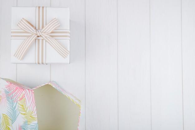Vista superior das caixas de presente em fundo branco de madeira, com espaço de cópia