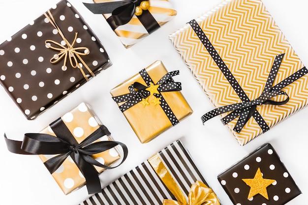 Vista superior das caixas de presente em vários desenhos pretos, brancos e dourados. postura plana. um conceito de natal, ano novo, evento de comemoração de aniversário.