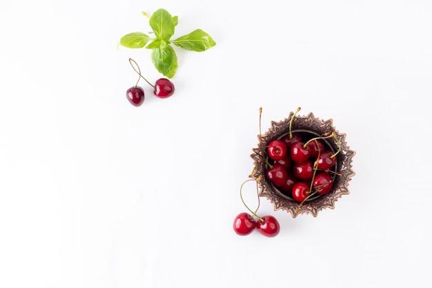 Vista superior das cerejas ácidas vermelhas dentro do prato marrom no fundo branco, cor de fruta, foto suave