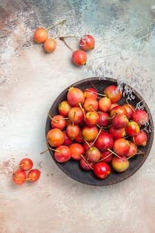 Vista superior das cerejas as cerejas apetitosas nos galhos das árvores da tigela