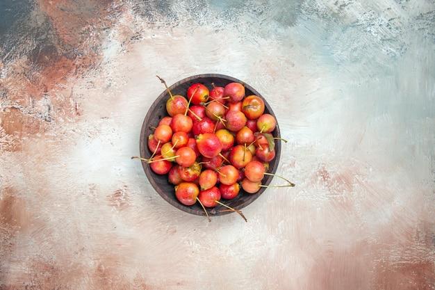 Vista superior das cerejas em uma tigela marrom de cerejas vermelho-amarelo na mesa rosa-branco-cinza