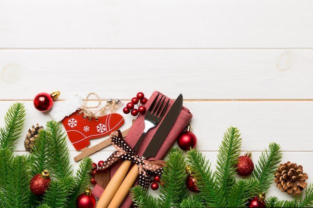 Vista superior das decorações de natal em fundo de madeira. garfo e faca no guardanapo amarrado com fita e espaço vazio para seu projeto. conceito de padrão de ano novo.