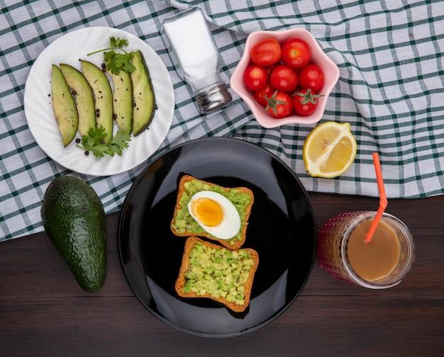 Vista superior das fatias de abacate em um prato branco com tomate abacate fresco, limão e fatias de pão torrado com polpa de abacate e ovo em toalha de mesa xadrez e madeira