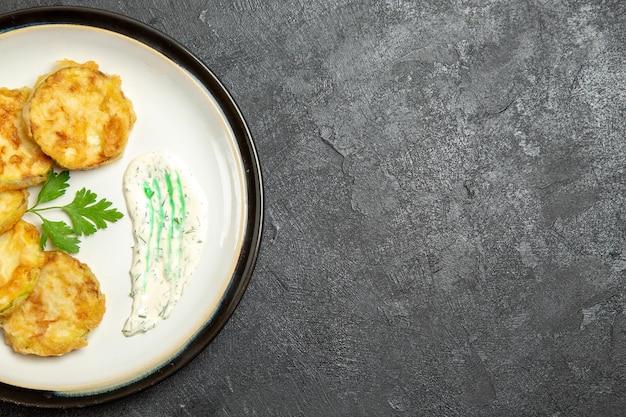 Vista superior das fatias de abóbora cozidas dentro do prato na superfície cinza