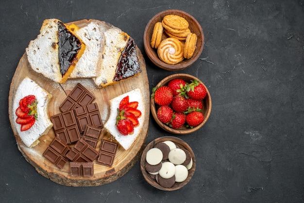 Vista superior das fatias de bolo com biscoitos de frutas e barras de chocolate na superfície escura