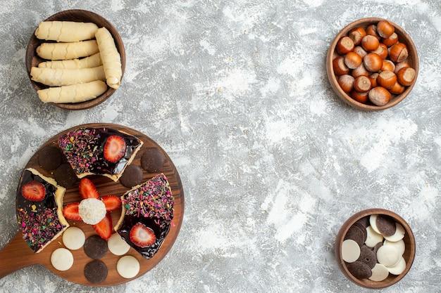 Vista superior das fatias de bolo com biscoitos e doces na superfície branca