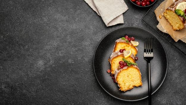 Vista superior das fatias de bolo no prato com frutas e espaço de cópia