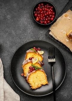 Vista superior das fatias de bolo no prato com frutas e garfo