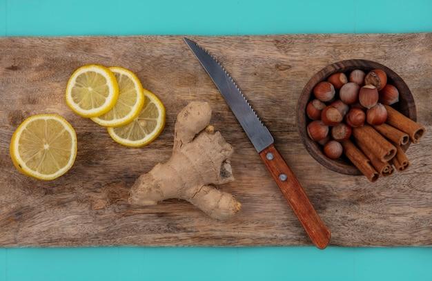 Vista superior das fatias de gengibre e limão com uma tigela de canela e nozes com uma faca na tábua de cortar no fundo azul