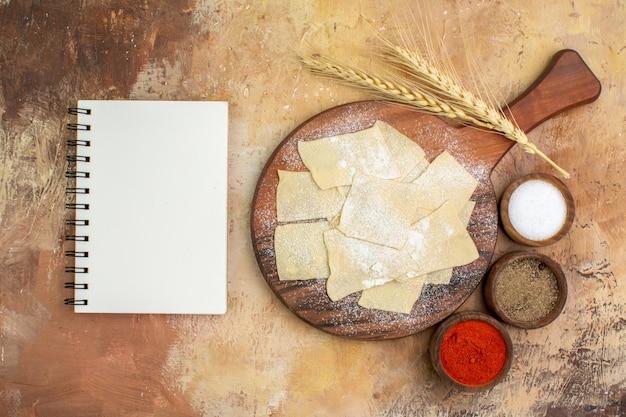 Vista superior das fatias de massa crua com farinha e temperos na mesa de madeira