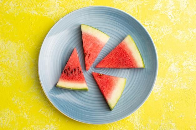 Vista superior das fatias de melancia dentro de uma placa azul na mesa amarela