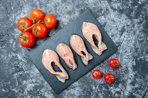 Vista superior das fatias de peixe cru no quadro negro de tomates frescos na mesa
