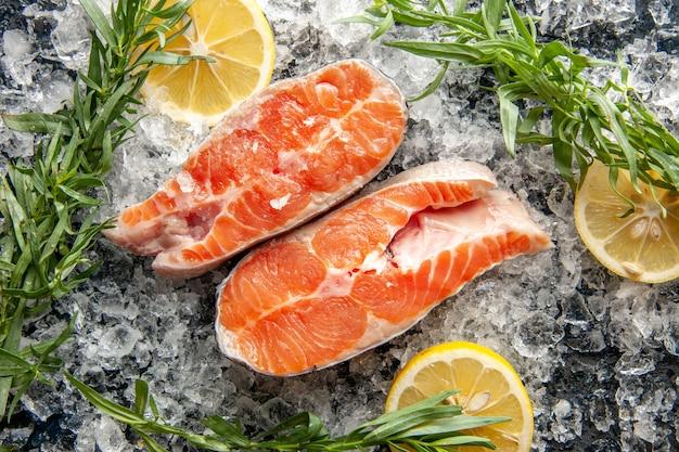Vista superior das fatias de peixe fresco com limão e gelo na mesa escura