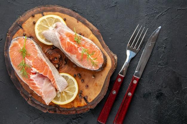 Vista superior das fatias de peixe fresco com limão e talheres na mesa escura