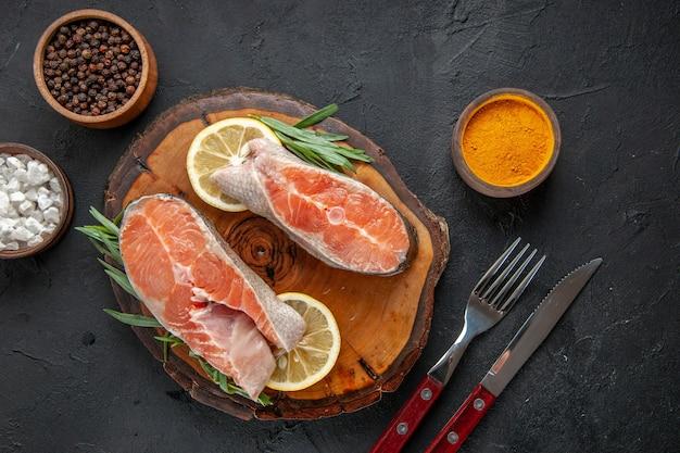 Vista superior das fatias de peixe fresco com limão e temperos na mesa escura