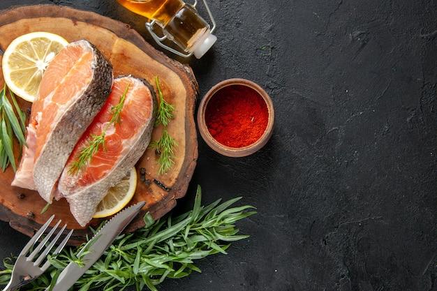 Vista superior das fatias de peixe fresco com rodelas de limão e temperos na mesa escura