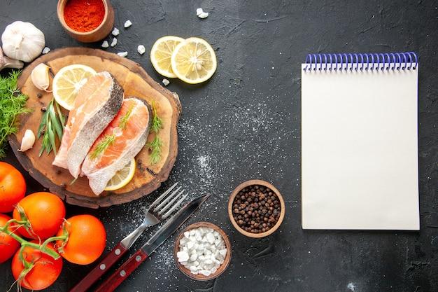 Vista superior das fatias de peixe fresco com temperos de tomate e rodelas de limão na mesa escura