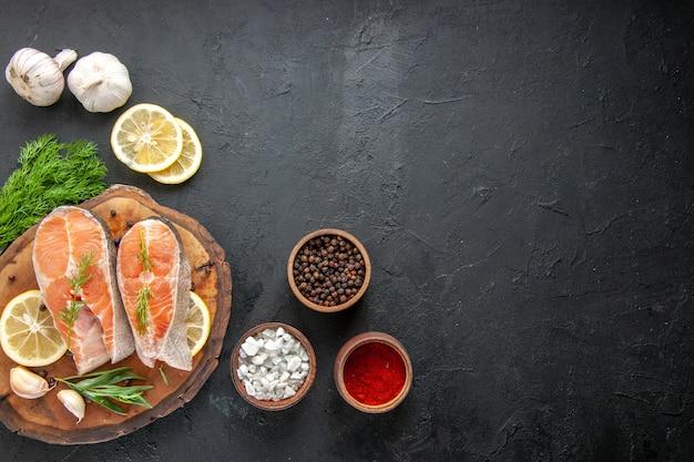 Vista superior das fatias de peixe fresco com temperos e rodelas de limão na mesa escura