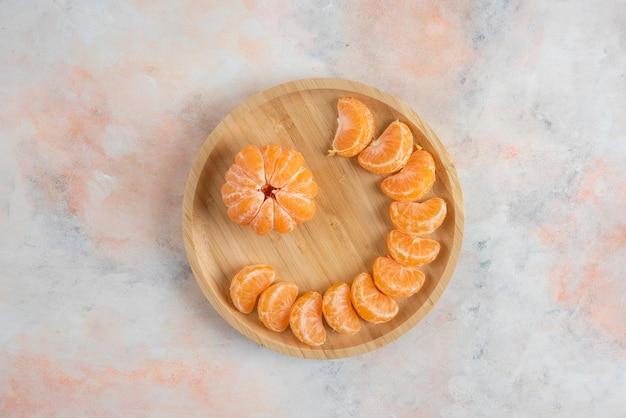 Vista superior das fatias de tangerina descascadas de clementina em uma placa de madeira