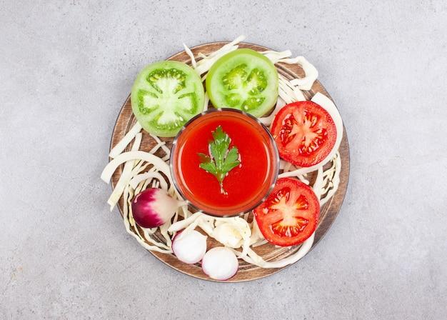 Vista superior das fatias de tomate verde e vermelho com rabanete na superfície de madeira.