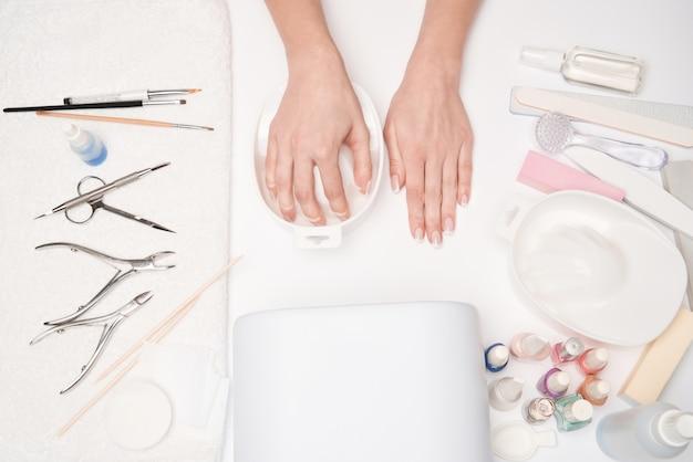 Vista superior das ferramentas de manicure e mulher preparando as mãos para fazer o procedimento de manicure