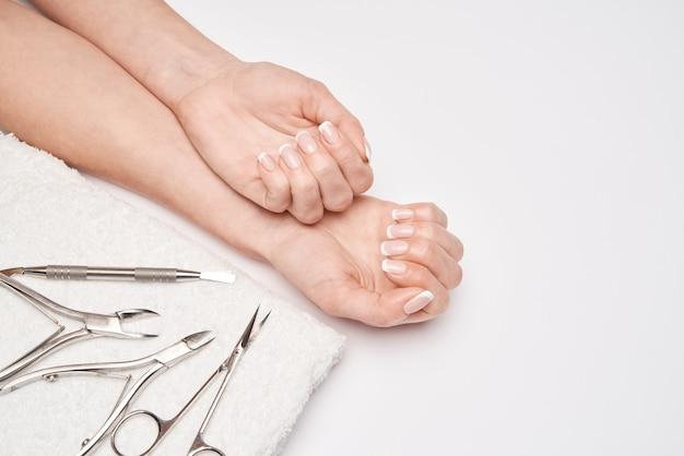 Vista superior das ferramentas de manicure em uma superfície branca.