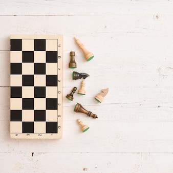 Vista superior das figuras de xadrez de madeira e tabuleiro de xadrez no fundo da mesa branca
