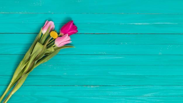 Vista superior das flores contra a mesa de madeira verde
