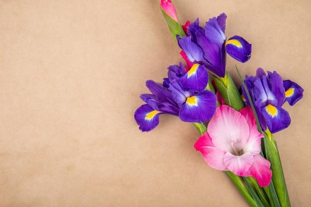 Vista superior das flores de íris e gladíolo de cor roxa e rosa escura, isoladas no fundo de textura de papel marrom com espaço de cópia