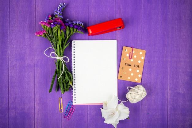 Vista superior das flores de statice de cor roxa e rosa com corda de grampeador caderno vermelho e cartão postal no fundo de madeira roxo