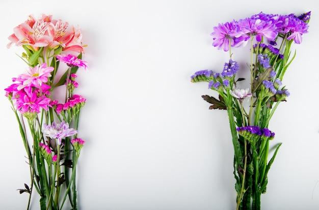 Vista superior das flores de statice e alstroemeria crisântemo de cor roxa e rosa escura, isoladas no fundo branco, com espaço de cópia