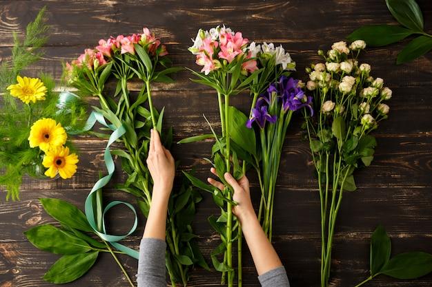 Vista superior das flores, florista em processo de fazer buquê