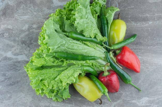 Vista superior das folhas de alface com pimentas coloridas.