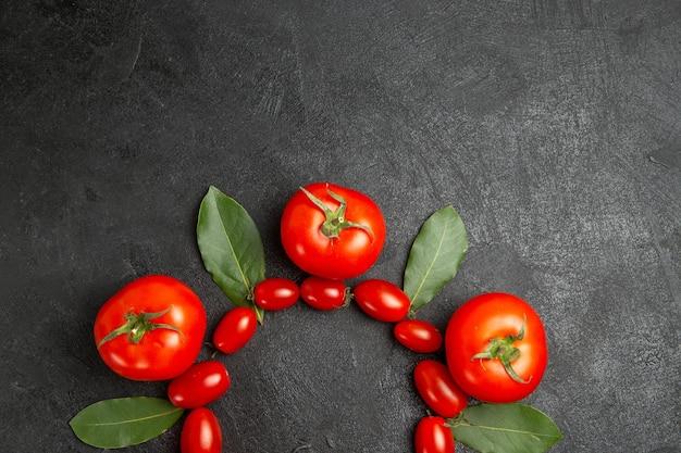 Vista superior das folhas de louro do tomate cereja e vermelho no fundo de um solo escuro com espaço de cópia