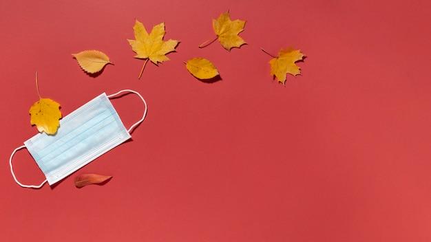 Vista superior das folhas de outono com máscara médica e espaço de cópia