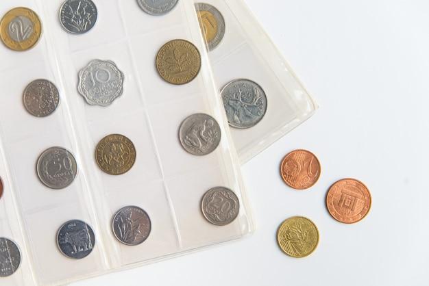 Vista superior das folhas e moedas numismáticas do álbum. coleção de moedas raras em fundo branco, com espaço de cópia