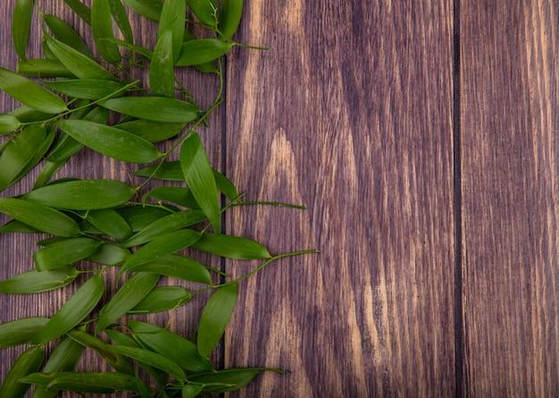 Vista superior das folhas no lado esquerdo e superfície de madeira