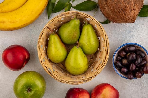 Vista superior das frutas como tigela de pêra com maçã, pêssego, banana, coco, bagas de uva com folhas no fundo branco
